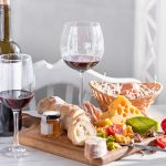 Wine, baguette and cheese on wooden background